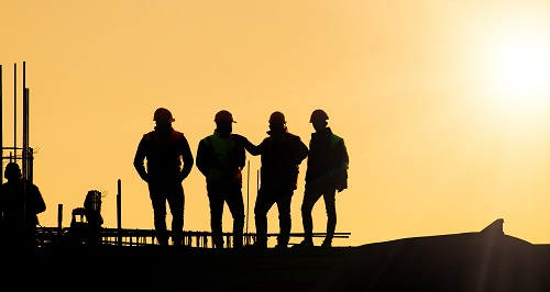 Silhouette of four engineers supervising works on construction site at sunset